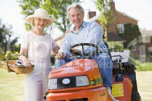 Couple outdoors with tools and lawnmower smiling