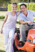 Couple outdoors with lawnmower smiling