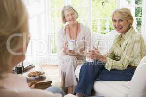 Three women in living room with coffee smiling