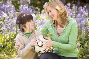 Mother and son outdoors holding ball smiling