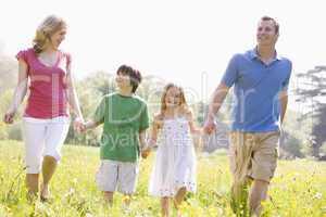 Family walking outdoors holding flower smiling