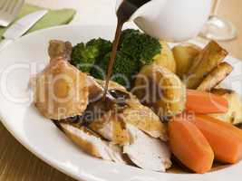 Gravy being Poured over a plate of Roast Chicken