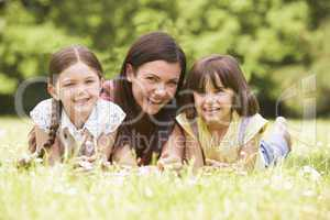Mother and daughters lying outdoors with flower smiling