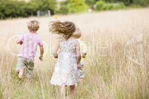 Three young children running outdoors