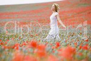 Woman walking in poppy field smiling