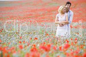 Couple in poppy field embracing and smiling