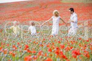 Family walking in poppy field holding hands smiling