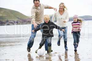 Family playing soccer at beach smiling