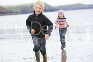 Two young children running on beach smiling