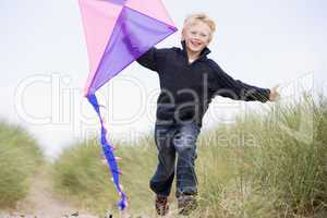 Young boy running on beach with kite smiling