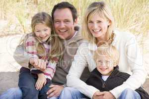 Family sitting on beach smiling