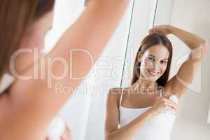 Woman in bathroom applying deodorant and smiling