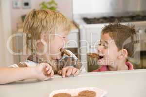 Two young boys in kitchen eating cookies smiling