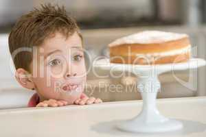 Young boy in kitchen looking at cake on counter