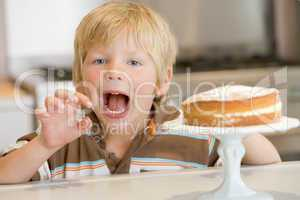 Young boy in kitchen with cake on counter