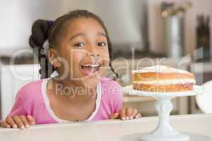 Young girl in kitchen looking at cake on counter smiling