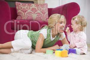 Mother in living room with baby eating banana and smiling