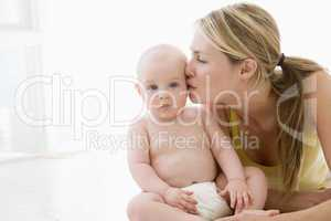 Mother kissing baby indoors