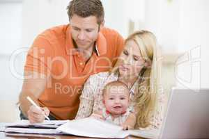 Couple and baby in dining room with laptop