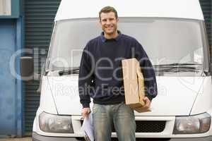 Delivery person standing with van holding clipboard and box smiling