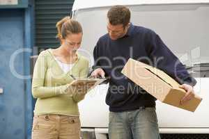 Two delivery people standing with van holding clipboard and box