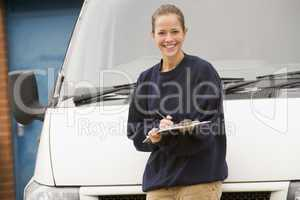 Delivery person standing with van writing in clipboard smiling
