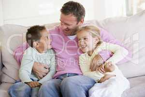 Man and two children sitting in living room smiling