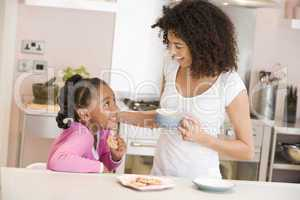 Woman and young girl in kitchen with cookies and coffee smiling