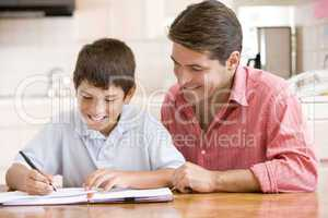Man helping young boy in kitchen doing homework and smiling