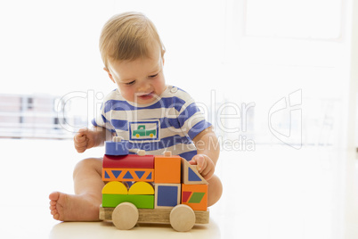 Baby indoors playing with truck