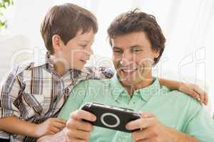 Man and young boy with handheld game smiling