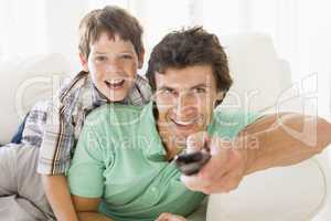 Man and young boy with remote control smiling