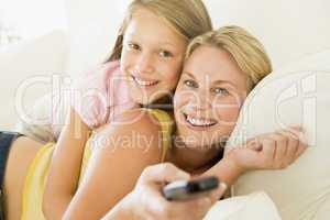 Woman and young girl with remote control embracing on sofa smili