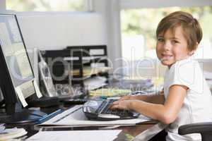 Young boy in home office with computer smiling