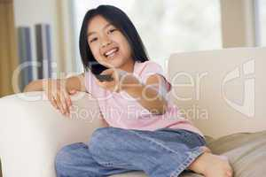 Young girl in living room with remote control smiling
