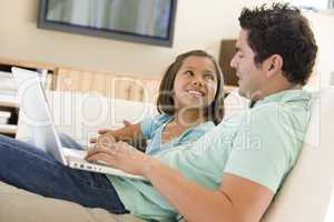 Man with young girl in living room with laptop smiling