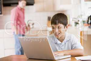 Young boy in kitchen with laptop and paperwork smiling with man