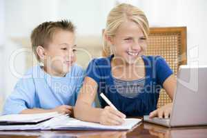 Two young children with laptop doing homework in dining room smi