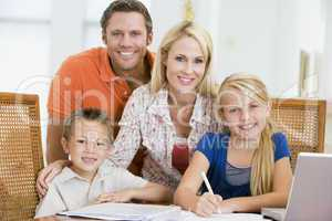 Couple helping two young children with laptop do homework in din