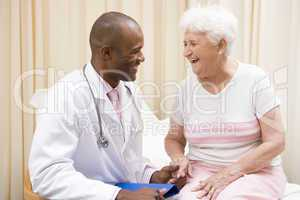 Doctor giving checkup to woman in exam room smiling