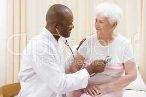 Doctor giving checkup with stethoscope to woman in exam room smi