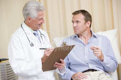 Doctor writing on clipboard while giving man checkup in exam roo