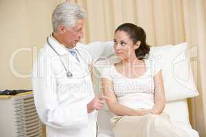 Doctor giving woman checkup in exam room