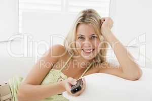 Woman in living room with remote control smiling