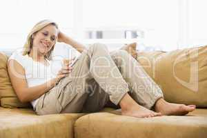Woman in living room listening to MP3 player smiling
