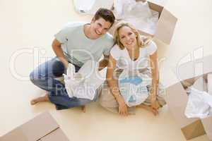Couple sitting on floor by open boxes in new home smiling