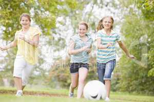 Three young girl friends playing soccer
