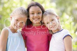 Three young girl friends standing outdoors smiling