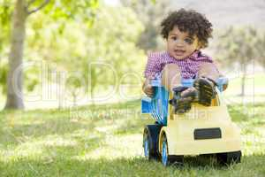 Young boy outdoors playing on toy dump truck smiling