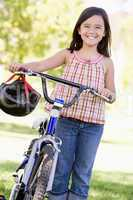 Young girl with bicycle outdoors smiling